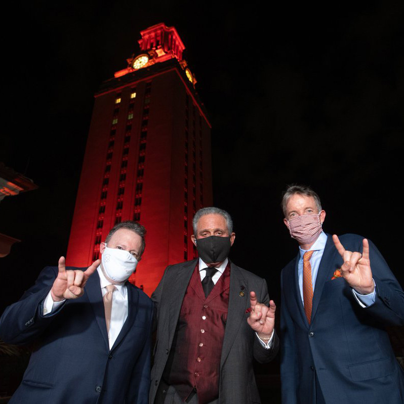 Jay Hartzell, Jay Bernhardt, and Arthur M. Blank giving the hook 'em horn gesture in front of tower