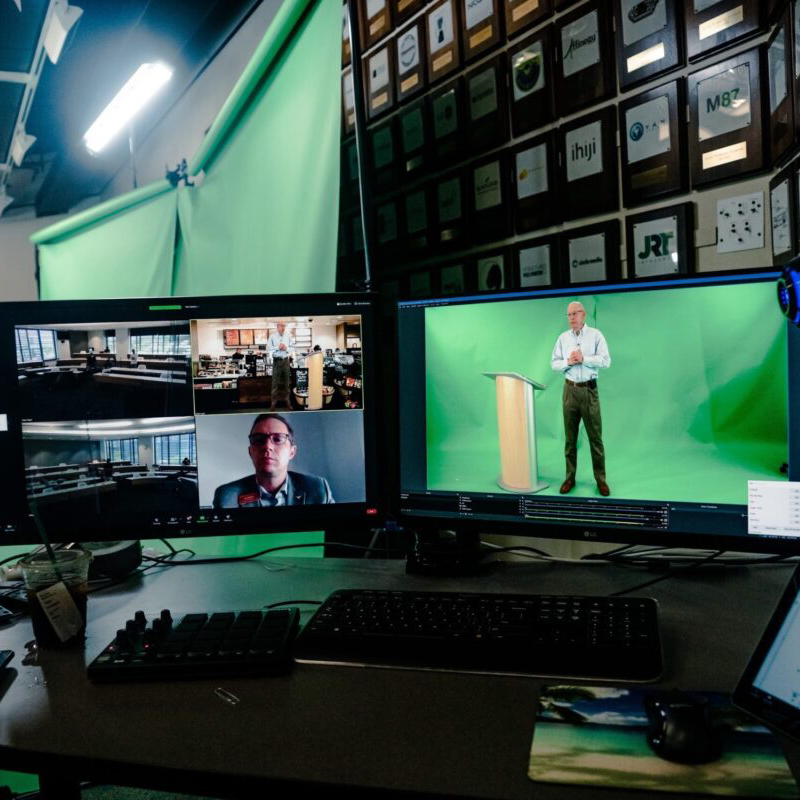 Two computer screens with one showing images of a classroom and one of a professor standing in front of green screen