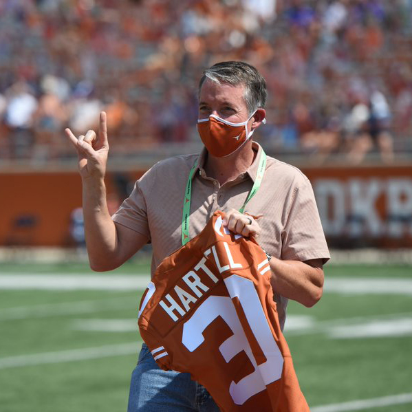 President Hartzell gives the hook 'em horns sign on the football field holding a football jersey with his name and the number 30