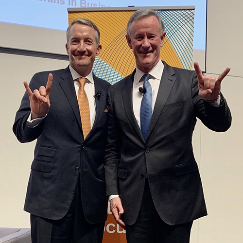 Interim President Jay Hartzell and former UT Chancellor William McRaven making the hook 'em horn hand gesture