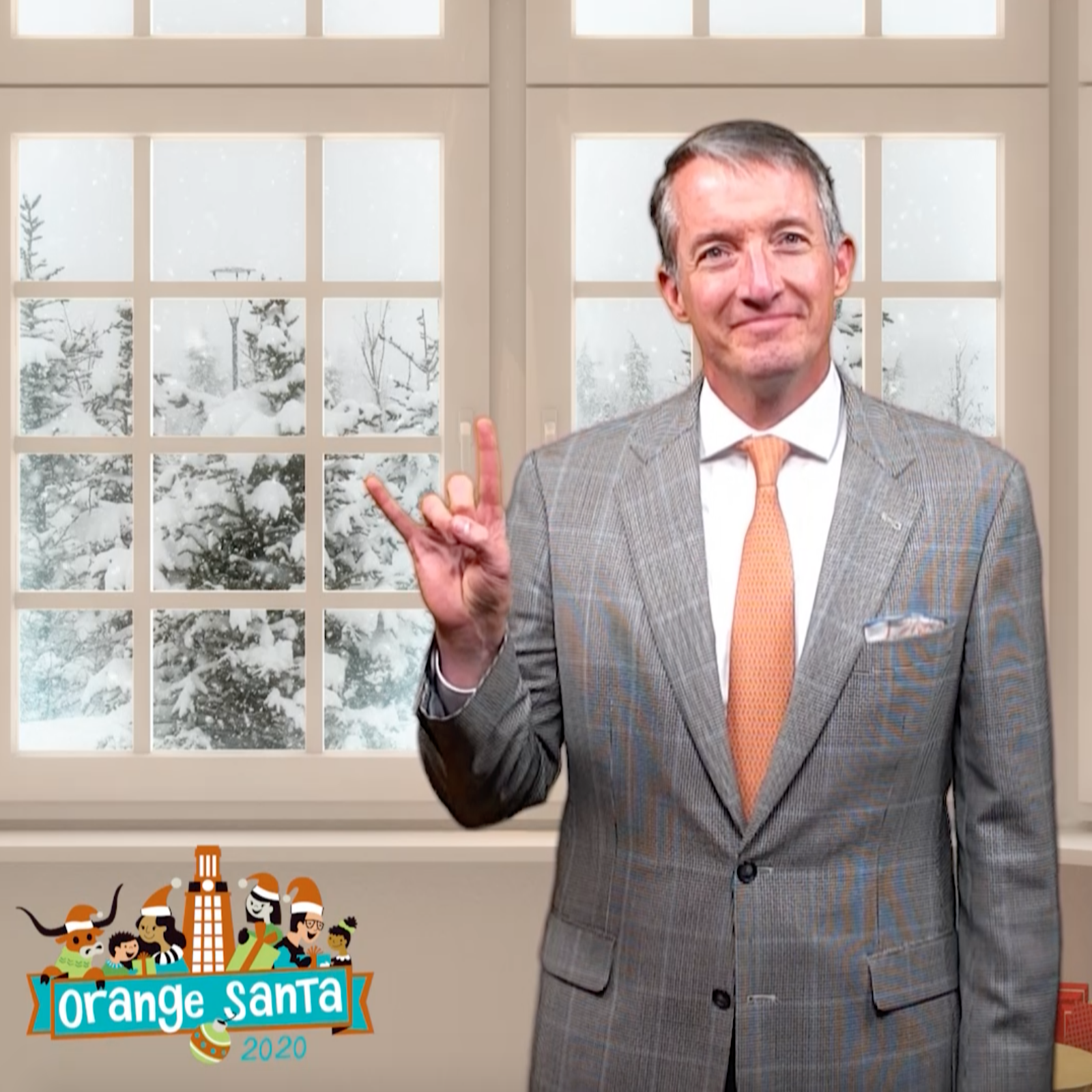 Jay Hartzell giving hook 'em horns hand gesture with snowy background behind him and Orange Santa logo in corner