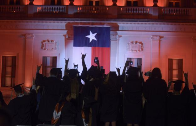 Students at commencement holding their hands up in the hook 'em horns gesture